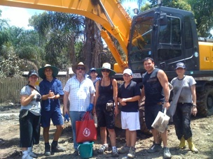 Muddy volunteers with shovels and a digging machine.