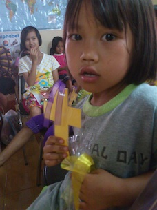 Little girl with handmade cross and giftbag. Photo by QCT.
